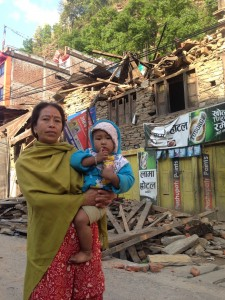 woman and baby in Nepal in front of damage 2015